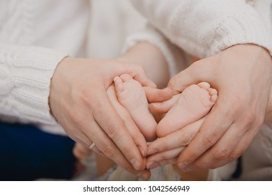 Mom and Father keep feet of newborn baby hand. Concept of tenderness, caring, love, family day