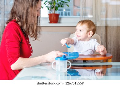 Mom feeding the baby holding out her hand with a spoon of food in the kitchen. Healthy baby nutrition. The emotions of a child while eating