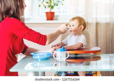 Mom feeding the baby holding out her hand with a spoon of food in the kitchen. Healthy baby food. The emotions of a child while eating