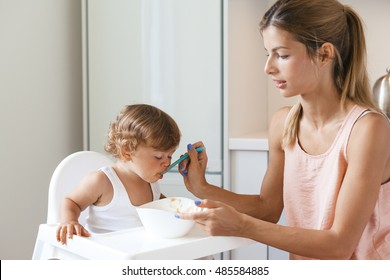 Mom feeding baby with spoon of 1,4 years old in white kitchen