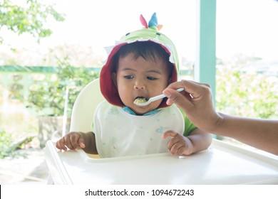Mom feeding food to baby
