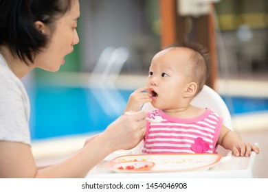 Mom feeding her baby girl with a spoon.First solid food for young kid.Baby weaning. Mom and little girl eat vegetables. Healthy nutrition for children. Parents feed kids.