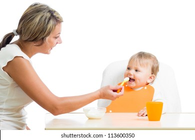 mom feeding her happy baby girl by spoon