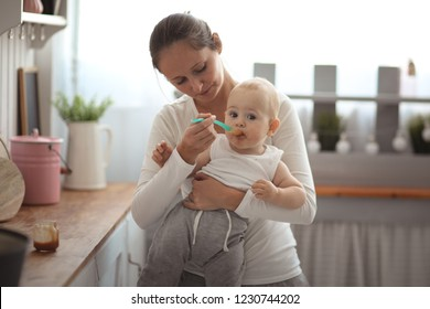 Mom feeds a happy baby with a spoon of fruit puree, light cozy real interior and lifestyle
