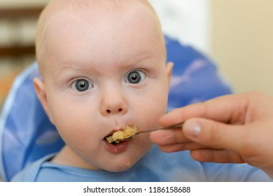Mom feeds her funny son from a spoon with applesauce