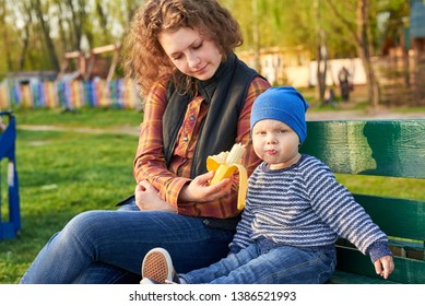 Mom feeds her little son with a fresh banana on a bench in the park. Healthy eating concept