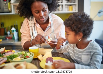 Mom with female kid in kitchen having diner