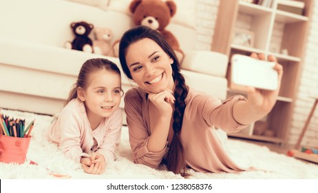 Mom Fun with Daughter. Rest at Home. Child Development. Mom and Daughter. Happy Person in Pajamas. Girl and Mother Lie on Carpet. Colour Pencils. Smiling Mom and Daughter. Make Selfie. Phone in Hand.