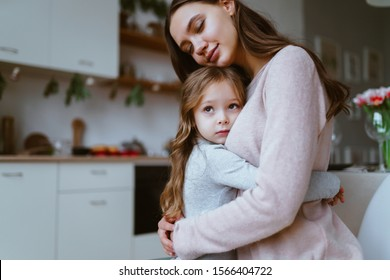 mom gently hugged her daughter, the girl snuggles up to her cheek with a frightened facial expression