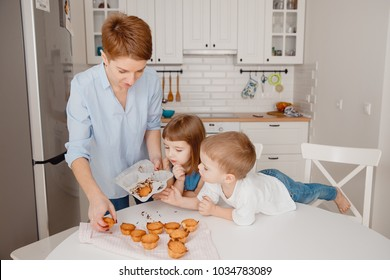 Mom gets cooked muffins out of shape, children look and help. Concept happy family prepares sweets.