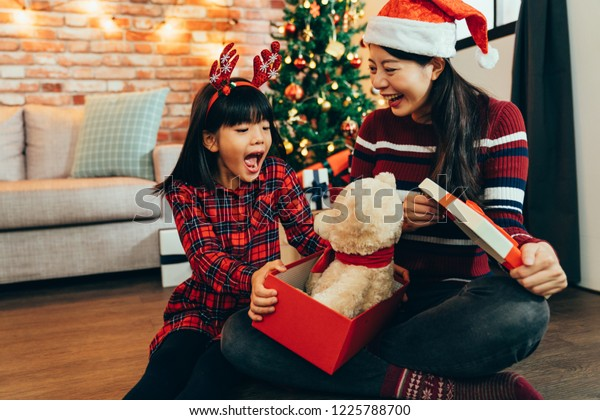 Mom give a little girl toy bear as christmas present on boxing day. young mother make lovely daughter a surprise on xmas holiday. beautiful child surprised by gift opening big mouth.