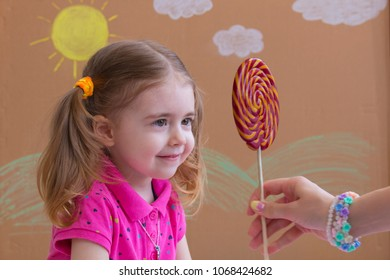 Mom gives the baby a lollipop, happy little girl eating big sugar lollipop, kid eat sweets. Beautiful little girl with lollipop