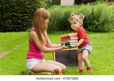 Mom gives daughter a lot of heavy books. Early child development