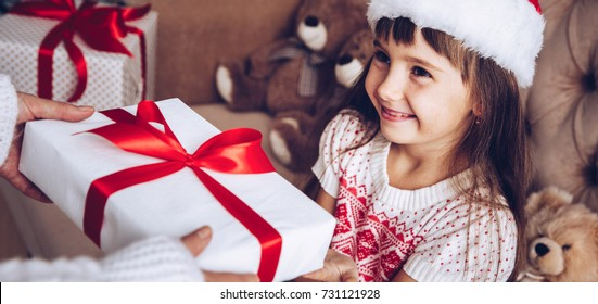 Mom gives a gift to her daughter, Christmas kids,child, portrait.Little girl in Santa Claus hat at home with Xmas tree.Close up,selective focus.Receive a present.