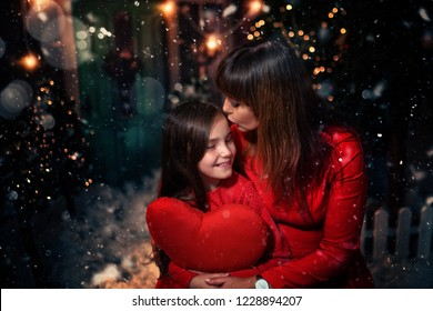 mom gives her daughter a kiss on a festive evening
