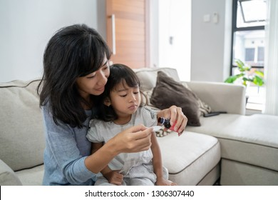 mom giving her little girl some medicine at home