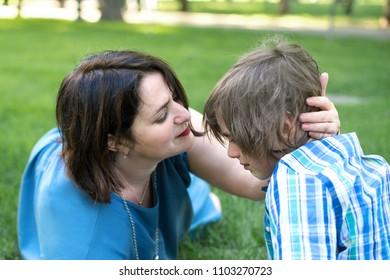Mom or grandmother calms a son or grandson.  The boy has a difficult age, he is upset about something and his mother tenderly calms him.