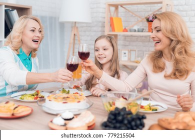 Mom and grandmother are drinking wine, a little girl is drinking juice. They have dinner at home. They have vegetables and sweets on their table.