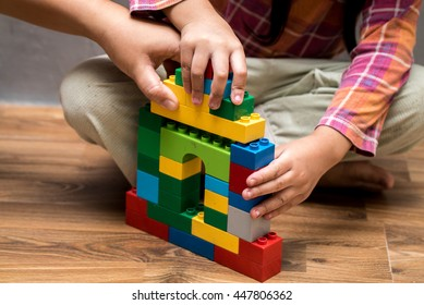 Mom hand and Asian kid girl building house from plastic blocks