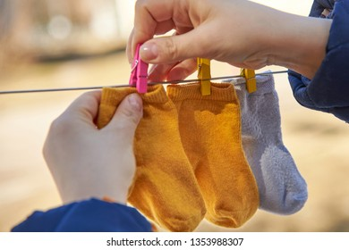 Mom hangs small baby socks on a clothesline for drying