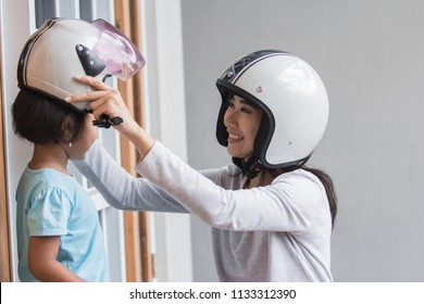 mom help her daughter to wear a helmet before riding a motor bike