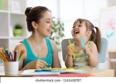 Mom helping her child daughter to work with colored paper