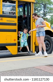 Mom helping small son off a school bus