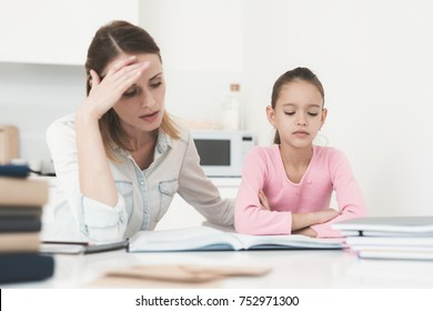 Mom helps my daughter do her homework in the kitchen. Mom and daughter are trying to solve the task. The girl does not understand her homework and her mother is unhappy with this.