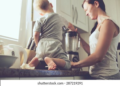 Mom with her 2 years old child cooking holiday pie in the kitchen to Mothers day, casual lifestyle photo series in real life interior. Focus on baby's foots.
