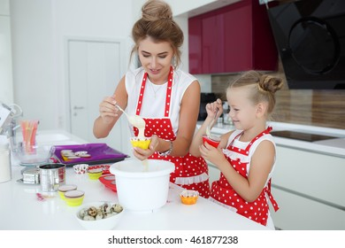 Mom with her 5 years old daughter are cooking in the kitchen to Mothers day, lifestyle photo series in bright home interior. Cute girl and her mother reading how to make dough at home.