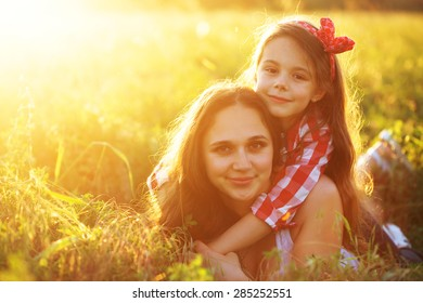 Mom and her 6 years old child playing in spring field