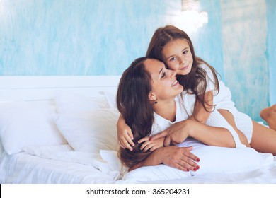 Mom with her 6 years old little daughter dressed in winter pajamas are relaxing and playing in the bed at the weekend together, lazy morning, warm and cozy scene.
