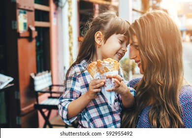Mom with her 6 years old daughter walking along city street and eating ice cream in front of the outdoor cafe. Good relations of parent and child. Happy moments together.