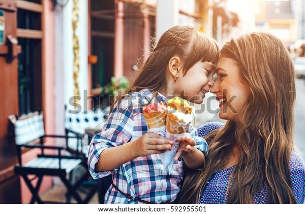 6歳の娘を連れて街を歩き、アウトドアカフェの前でアイスクリームを食べている。親子の良い関係。幸せな瞬間を一緒に。