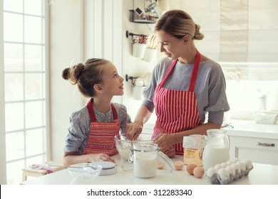Mom with her 9 years old daughter are cooking in the kitchen to Mothers day, lifestyle photo series in bright home interior