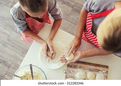 Mom with her 9 years old daughter are cooking in the kitchen to Mothers day, lifestyle photo series in bright home interior, top view point