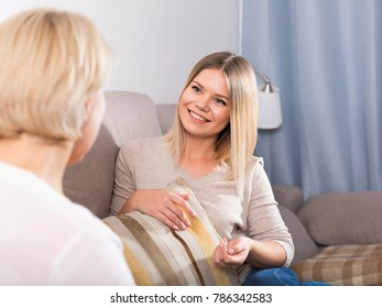 Mom and her adult daughter talking at home sitting on the couch