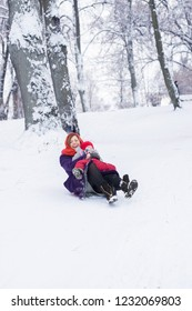 Mom and her child sledding in the winter park
