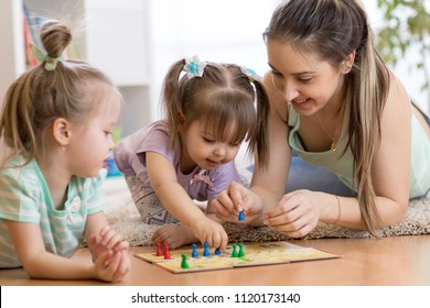 Mom and her children playing in ludo board game