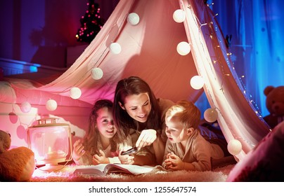 Mom and her children reading a book in a tent