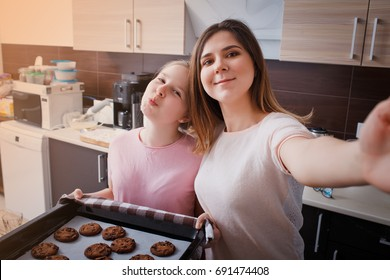 Mom and her daughter bake cookies at home in the modern kitchen and making selfie