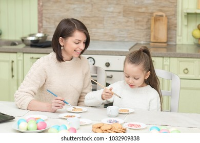 Mom and her daughter baking together and decorating the cookies