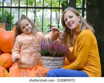 Mom and her daughter hold a basket of swords against the background of orange pumpkin. Family Portrait
