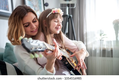 Mom with her daughter playing electric guitar together at home, happy family