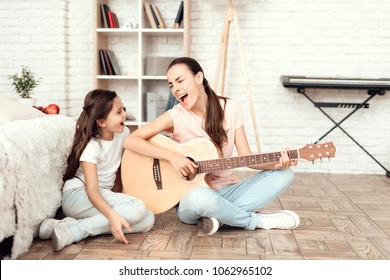 Mom and her daughter are sitting on the floor at home and playing the guitar. They sing to the guitar. Behind them is a bookshelf, a synthesizer and a white wall.