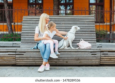 Mom and her daughter sitting on a bench with dog. Love of mother and daughter. Mothers day.