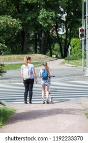 Mom and her daughter stand on pedestrian crossing on red light, waiting green light