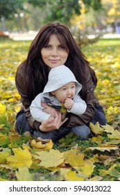Mom and her little baby sitting on the grass in the park