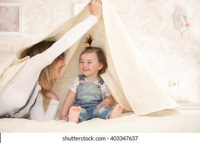 Mom with her  little daughter are relaxing and playing in the bed