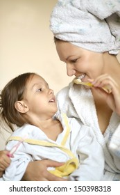 Mom and her little daughter in white bathrobes